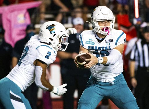 Coastal Carolina quarterback Grayson McCall (10) hands off the football to running back Reese White (2) during the first half of an NCAA football game against Louisiana-Lafayette in Lafayette, La., Wednesday, Oct. 14, 2020.