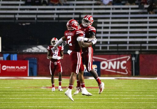 Louisiana-Lafayette linebackers Lorenzo McCaskill (2) and Tyler Guidry (33) celebrate a defensive stop during the first half of an NCAA football game against Coastal Carolina in Lafayette, La., Wednesday, Oct. 14, 2020.