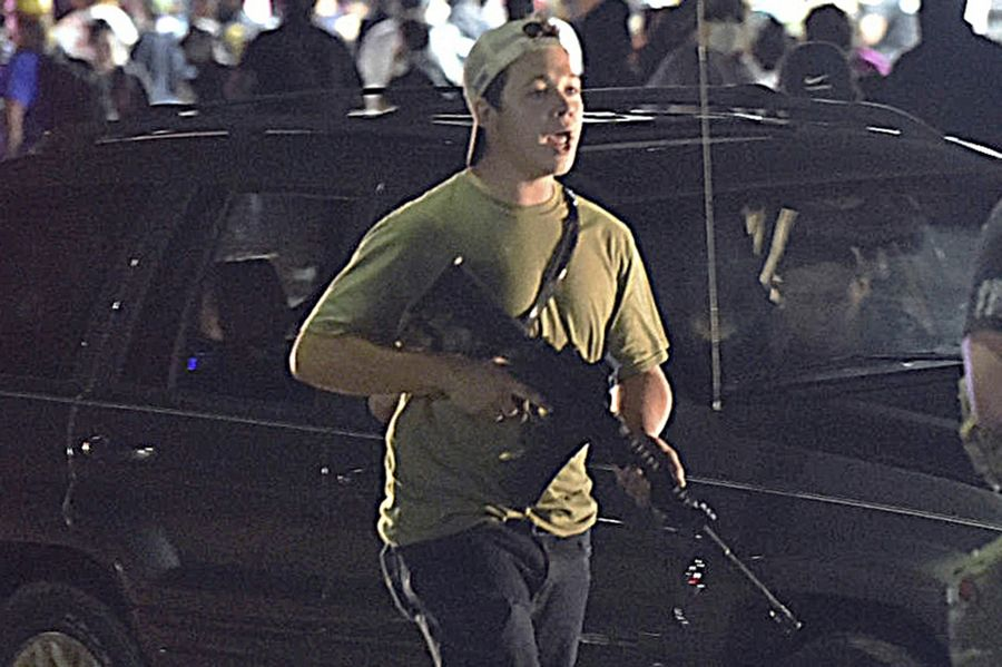 Kyle Rittenhouse carries a weapon as he walks along Sheridan Road in Kenosha, Wis., during unrest two days after the police shooting of Jacob Blake.