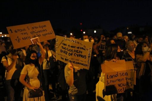 Protesters hold up placards during a demonstration against corruption at a conference center in the capital Nicosia, Cyprus, Wednesday, Oct. 14, 2020. Protesters calling for the resignation of Cyprus' Parliamentary Speaker Demetris Syllouris amid corruption allegations involving the country's now defunct citizenship-for-investment program.