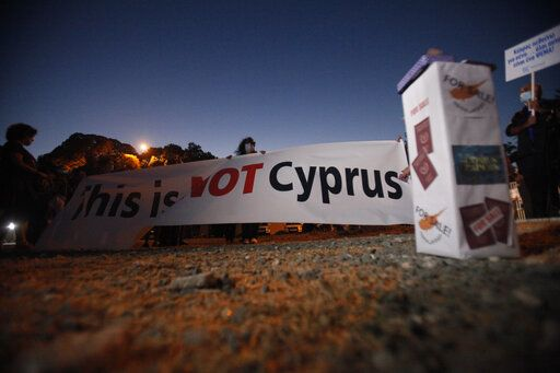 "A protester holds a banner reading ""This is Not Cyprus"" as a box right shows Cyprus Passports the Cyprus flag reading ""For Sale"" during a demonstration against government corruption, at a conference center in the capital Nicosia, Cyprus, Wednesday, Oct. 14, 2020. Protesters calling for the resignation of Cyprus' Parliamentary Speaker Demetris Syllouris amid corruption allegations involving the country's now defunct citizenship-for-investment program."