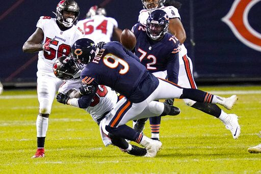 Chicago Bears quarterback Nick Foles (9) fumbles the ball as he's sacked by Tampa Bay Buccaneers outside linebacker Jason Pierre-Paul (90) during the second half of an NFL football game in Chicago, Thursday, Oct. 8, 2020. The Bears recovered the fumble,
