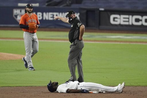 Second base umpire Jeff Nelson indicates to Tampa Bay Rays Randy Arozarena to get off the field after he was forced out by Houston Astros shortstop Carlos Correa during the third inning in Game 7 of a baseball American League Championship Series, Saturday, Oct. 17, 2020, in San Diego.