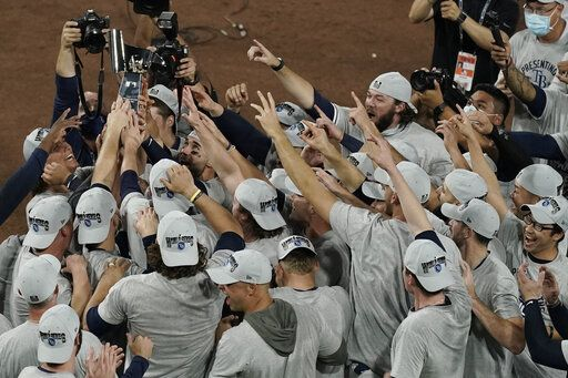 Tampa Bay Rays hold the American League championship trophy following their victory against the Houston Astros in Game 7 of a baseball American League Championship Series, Saturday, Oct. 17, 2020, in San Diego. The Rays defeated the Astros 4-2 to win the series 4-3 games.