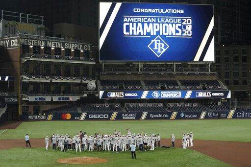 Tampa Bay Rays stand at midfield to receive the American League championship trophy following their victory against the Houston Astros in Game 7 of a baseball American League Championship Series, Saturday, Oct. 17, 2020, in San Diego. The Rays defeated the Astros 4-2 to win the series 4-3 games.