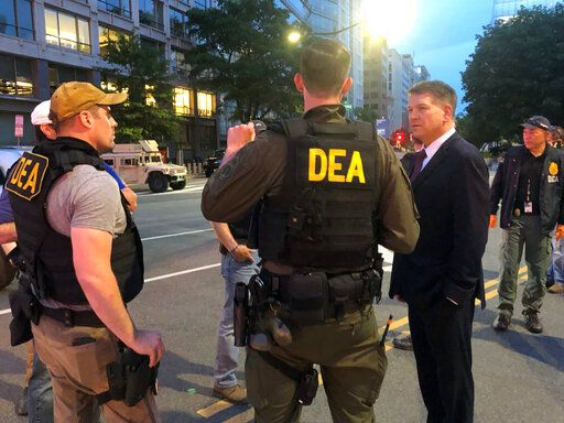 In this Wednesday, June 3, 2020, photo Acting Drug Enforcement Administrator Timothy Shea, right, visits with DEA agents at a checkpoint in Washington. More than 1,500 people have been arrested in the last three months as part of a Drug Enforcement Administration project focusing on violent crime. The initiative, nicknamed Project Safeguard, comes as President Donald Trump has touted similar operations as a much-needed answer to a spike in crime. It's also to showcase what he says is his law-and-order prowess, claiming he's countering rising crime in cities run by Democrats. Acting DEA Administrator Tim Shea tells the AP that since the operation launched in August, 1,521 people have been arrested in both state and federal cases in cities across the U.S. and 2,135 firearms have been seized.