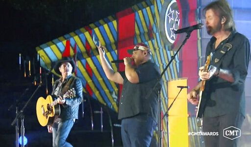 "In this video image provided by CMT, Kix Brooks, from left, Luke Combs and Ronnie Dunn perform ""1, 2 Many'� during the Country Music Television awards airing on Wednesday Oct. 21, 2020. (CMT via AP)"