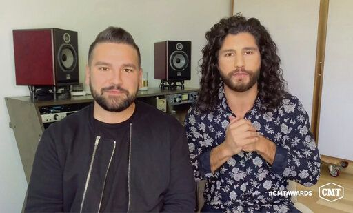 In this video image provided by CMT, Shay Mooney, left, and Dan Smyers, of Dan + Shay, accept the duo video of the year for 'œI Should Probably Go To Bed'� during the Country Music Television awards airing on Wednesday, Oct. 21, 2020. (CMT via AP)