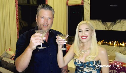 In this video image provided by CMT, Blake Shelton, left, and Gwen Stefani  toast as they accept the collaboration of the year award for 'œNobody But You'� during the Country Music Television awards airing on Wednesday, Oct. 21, 2020. (CMT via AP)