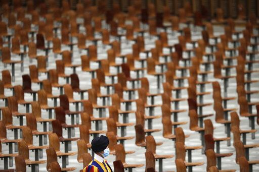 A Swiss guard walks past empty seats on the occasion of the weekly general audience at the Vatican, Wednesday, Oct. 21, 2020.