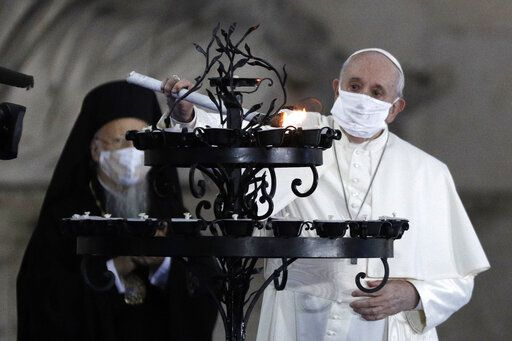 Pope Francis lights a candle for peace during an inter-religious ceremony for peace in the square outside Rome's City Hall, Tuesday, Oct. 20, 2020