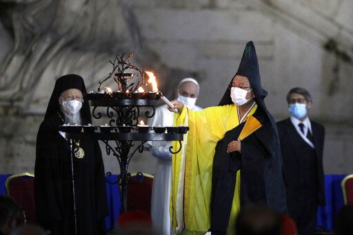 Buddhist monk Shoten Minegishi lights a candle for peace as Bartolomew I, Patriarch of Constantinopolis, Pope Francis and Haim Korsia, Chief Rabbi of France, look on, during an inter-religious ceremony for peace in the square outside Rome's City Hall, Tuesday, Oct. 20, 2020
