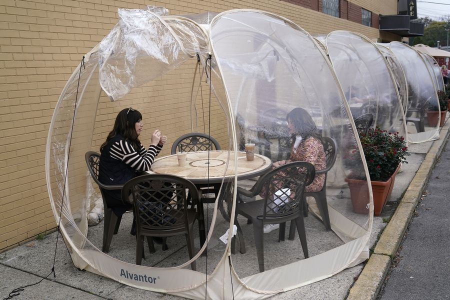 Aviva Markowitz, left, and Rivka Alter enjoy a drink in a protective bubble at the Lazy Bean Cafe in Teaneck, New Jersey. The United States is approaching a record for the number of new daily coronavirus cases in the latest ominous sign about the disease's grip on the nation.