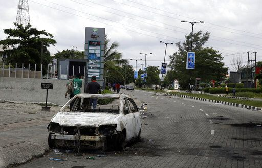 A burnt out car is seen on Lekki road in Lagos Friday, Oct. 23, 2020. Resentment lingered with the smell of charred tires Friday as Nigeria's streets were relatively calm after days of protests over police abuses, while authorities gave little acknowledgement to reports of the military killing at least 12 peaceful demonstrators earlier this week.
