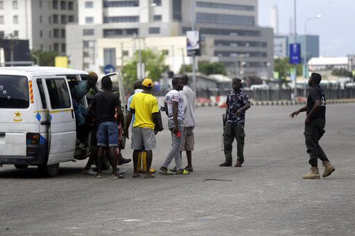 Police officers stop and search a bus carrying passengers around Lekki toll gate in Lagos Friday, Oct. 23, 2020. Resentment lingered with the smell of charred tires Friday as Nigeria's streets were relatively calm after days of protests over police abuses, while authorities gave little acknowledgement to reports of the military killing at least 12 peaceful demonstrators earlier this week.