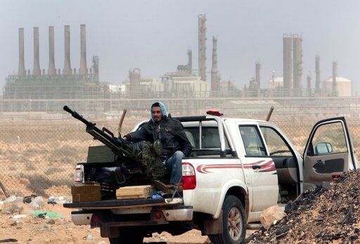 "FILE - In this March 5, 2011 file photo, an anti-government rebel sits with an anti-aircraft weapon in front an oil refinery in Ras Lanouf, eastern Libya. The United Nations said Friday, Oct. 23, 2020, that the two sides in Libyan military talks had reached a ""historic achievement"" with a permanent cease-fire agreement across the war-torn North African country."