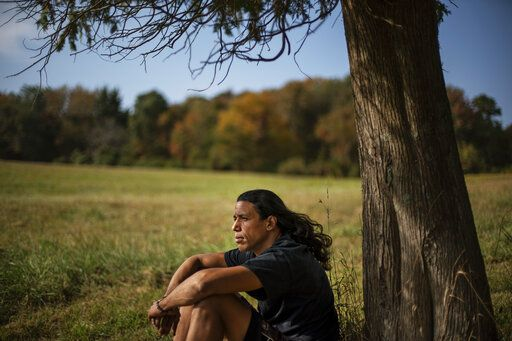 "Annawon Weeden, 46, a member of the Mashpee Wampanoag Tribe, sits for a portrait outside his home in Oakdale, Conn., Friday, Sept. 25, 2020. ""How do you pay somebody for that?"" said Weeden when asked if governments should make financial reparations to Native people. ""The most valuable thing anyone can have or possess ever is time and you don't get that time back. I don't get my ancestors back. It's degrading to think that you could buy your way out of what you put us in. Actions speak for themselves,"" Weeden said. ""You don't got to pay me a dime. Clean up your community, show some respect. Pay the land the respect. It's never about me. It's about this land. I'm only here for a short time. This land had to last a lot longer. Your children are going to have to inherit this. What do you want to leave them? Let's look about our children and how our children's lives are going to turn out because if we can't get things to go better for them, we've all failed."""