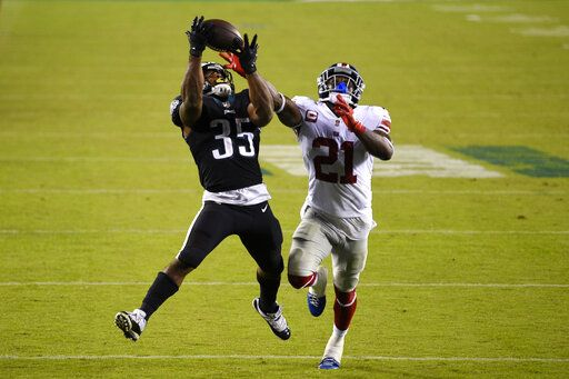 Philadelphia Eagles' Boston Scott, left, catches a touchdown pass against New York Giants' Jabrill Peppers during the second half of an NFL football game, Thursday, Oct. 22, 2020, in Philadelphia.