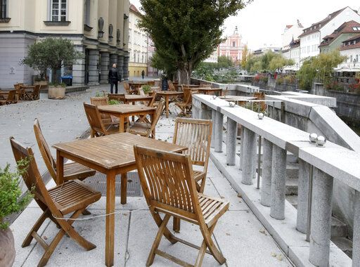 Cafe chairs are empty due to Covid-19 restrictions in downtown Ljubljana, Slovenia, Monday, Oct. 19, 2020. Slovenia has introduced a nationwide overnight curfew in an effort to control the spread of the new coronavirus. The authorities on Monday also said that gatherings will be limited to six people and movement among regions will be banned.