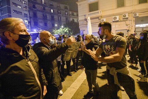 A protester, right, argues with a plainclothes police officer late Friday, Oct. 23, 2020, in Naples, southern Italy.  Protesters in Naples, angry over a just-imposed 11 p.m. to 5 a.m. regional curfew and by the local governor's vow to put the region under lockdown to try to tame surging COVID-19 infections, clashed with police on Friday night. (Alessandro Pone/LaPresse via AP)