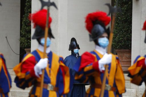 Vatican Swiss Guards wearing masks to curb the spread of COVID-19 stand attention the St. Damaso courtyard on the occasion of the visit of Spain's Prime Minister Pedro Sanchez to Pope Francis, at the Vatican, Saturday, Oct. 24, 2020.