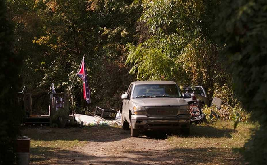 A confederate flag hangs from a porch on a property in Munith, Mich., Friday, Oct. 9, 2020, where law enforcement officials said suspects accused in a plot to kidnap Michigan Democratic Gov. Gretchen Whitmer met to train and make plans. Pete Musico and Joseph Morrison, who officials said lived at the Munith property, have been charged in the plot. A federal judge said Friday, Oct. 16, 2020, prosecutors have enough evidence to move toward trial for five Michigan men accused of plotting to kidnap Democratic Gov. Gretchen Whitmer. (Nicole Hester/Ann Arbor News via AP)