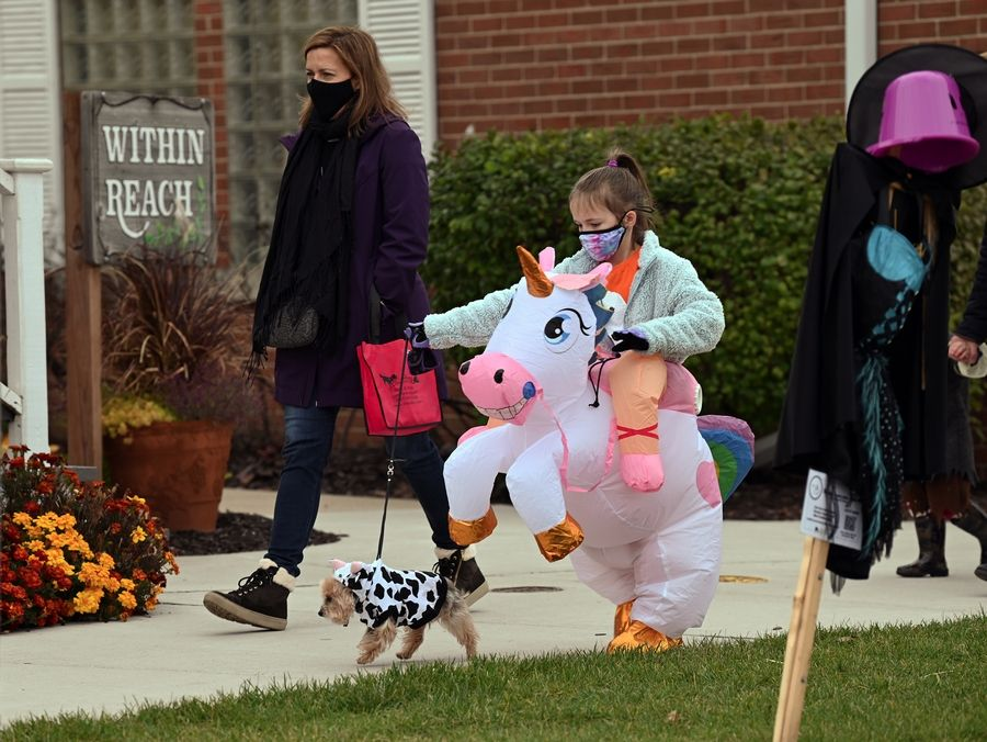 Grace Elliott, 7, a second-grader from Long Grove, rode a unicorn alongside her mother, Jolie Elliott, and Charlie, their male Yorkshire terrier, on Sunday during the third annual Pet Costume Parade in Long Grove.