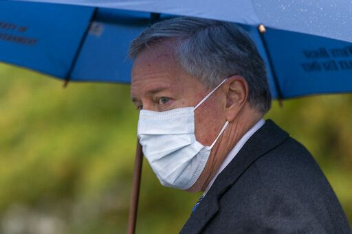 White House chief of staff Mark Meadows glances as he responds to reporters questions outside the West Wing on the North Lawn of the White House, Sunday, Oct. 25, 2020, in Washington.