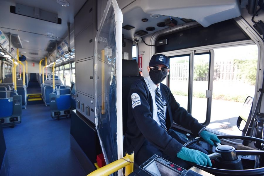 Pace driver Mike Jozwiak has a face mask and plastic barrier to guard against COVID-19 transmission. The bus agency says ridership is down by 50%, the 2021 budget anticipates a $53.6 million shortfall and 73 bus routes are temporarily canceled.