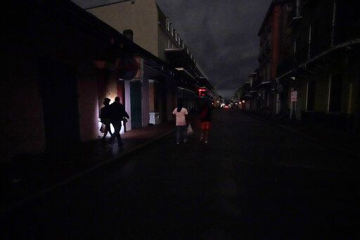 A darkened Bourbon Street is illuminated only by passers-by with lights and car headlights in the French Quarter in New Orleans, Wednesday, Oct. 28, 2020. Hurricane Zeta passed through today leaving much of the city and metro area without power.