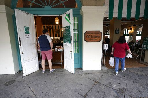 Patrons enter Cafe du Monde Coffee Stand in the French Quarter in New Orleans, Wednesday, Oct. 28, 2020. Businesses that were boarded up for previous hurricanes this season remain open this time as Hurricane Zeta approaches, expected to make landfall as a category 2 hurricane in the afternoon.