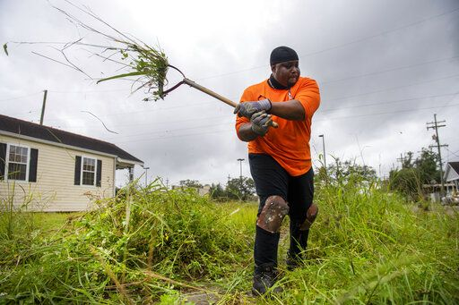 Hurricane Zeta winds make the grass that Teddy Johnson, 58, was cutting from a ditch at his family home on Flood Street in New Orleans fly in the air on Wednesday, Oct. 28, 2020. Johnson said he was quickly clearing the ditch so that any flood or rain water from the storm could drain more quickly. Johnson, who lives in Houston, Texas, moved there after Hurricane Katrina, but returns to his family's New Orleans home to help maintain it. (Chris Granger/The Times-Picayune/The New Orleans Advocate via AP)
