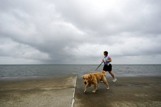 Jane McDow walks with her dog 'Duke' along the Lake Pontchartrain seawall in New Orleans, Wednesday, Oct. 28, 2020. Hurricane Zeta is expected to make landfall this afternoon as a category 2 storm.
