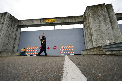 A Plaquemines Parish sheriff deputy walks away after workers closed a floodwall gate on Hwy 39 in Poydras, La., Wednesday, Oct. 28, 2020. Hurricane Zeta is expected to make landfall this afternoon as a category 2 storm.