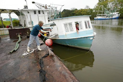 Perry Menesses tosses a rope to Will Guillot as they wanted to secure their boat with more rope after hearing that Hurricane Zeta has increased in strength, in Violet, La., Wednesday, Oct. 28, 2020. Hurricane Zeta is expected to make landfall this afternoon as a category 2 storm.