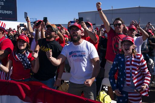 Supporters of President Donald Trump cheer as he arrives for a campaign rally at Laughlin/Bullhead International Airport, Wednesday, Oct. 28, 2020, in Bullhead City, Ariz.