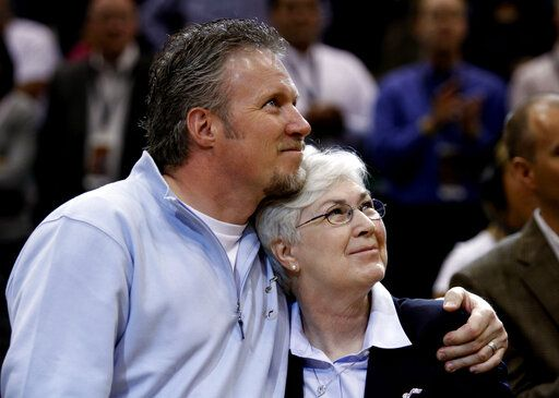FILE - In this April 14, 2010, file photo, Greg Miller, left, and Gail Miller, son and wife of the late Larry H. Miller, hug while looking up at the jersey that had been retired in the name of Larry H. Miller, at Energy Solutions Arena during halftime of an NBA basketball game between the Utah Jazz and the Phoenix Suns in Salt Lake City. The majority interest of the Utah Jazz is being sold to technology entrepreneur Ryan Smith, a move that when formally approved by the NBA will end the Miller family's 35-year run as owners of the franchise. The Jazz said Wednesday, Oct. 28, 2020, that 'œdefinitive agreements'� have been struck with Smith on the sale of the team, Vivint Arena, the team's G League affiliate and management of a Triple-A baseball club. Part of those agreements call for the team to remain in Utah.