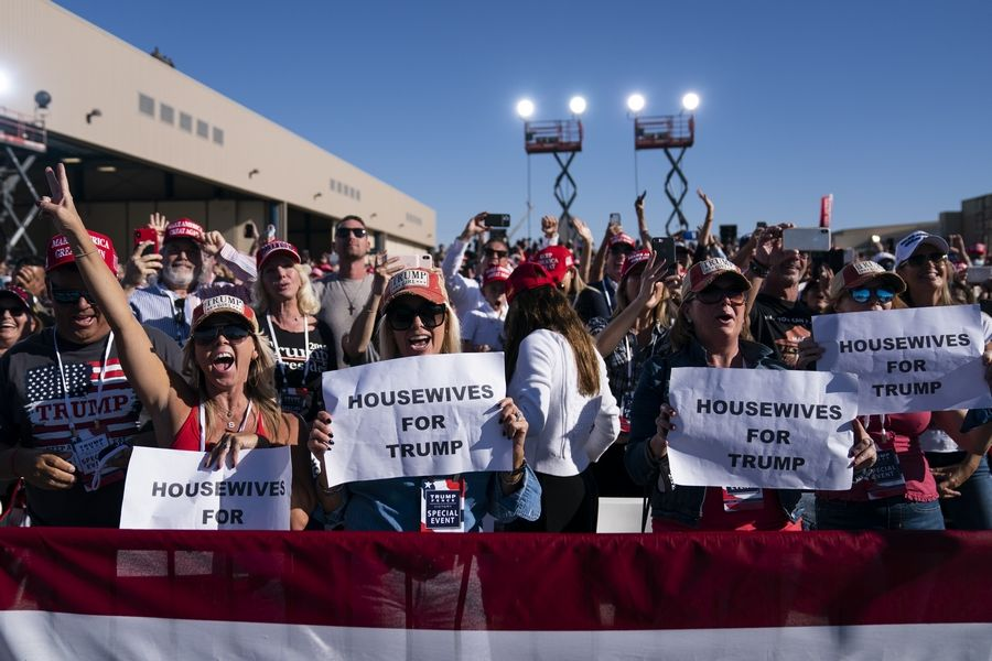 Supporters of President Donald Trump listen to him speak Wednesday during a campaign rally at Phoenix Goodyear Airport in Goodyear, Arizona. Trump is painting an apocalyptic portrait of American life if Democrat Joe Biden gets elected. The president claims that if the Democrat takes over, the suburbs wouldn't be the suburbs anymore, the economy would slump into its worst depression ever and police departments would cease to exist.