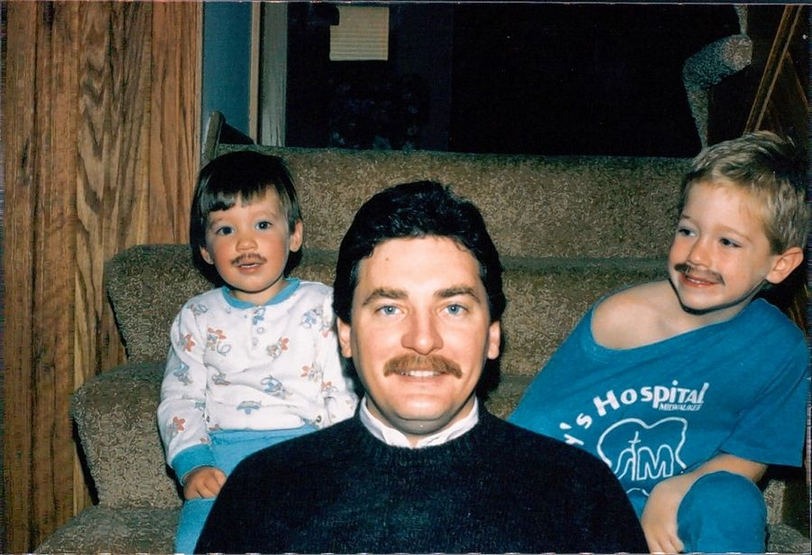 "Patrick Canning, left, and his brother, Nick, sport pretend mustaches to match their dad, Terry, as children growing up in Hawthorn Woods. Patrick Canning is now an author, and his newest novel is titled ""Hawthorn Woods."""