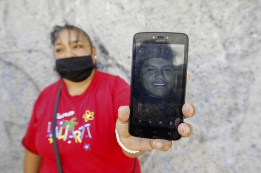 Leticia Valencia Cruz shows a photo of her son Jose Manuel who was disappeared in 2018, near the site where family members who search for disappeared relatives have found 59 bodies, in Salvatierra, Guanajuato state, Mexico, Thursday, Oct. 29, 2020. A Mexican search group said Wednesday it has found 59 bodies in a series of clandestine burial pits in the north-central state of Guanajuato, and that more could still be excavated.