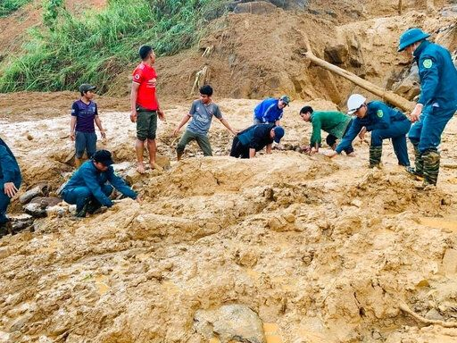 Soldiers and villagers dig through mud after a landslide swamps a village in Phuoc Loc district, Quang Nam province, Vietnam on Thursday, Oct. 29, 2020. Three separated landslides triggered by typhoon Molave killed over a dozen villagers and left dozens more missing in the province as rescuers scramble to recover more victims. (Lai Minh Dong/VNA via AP)