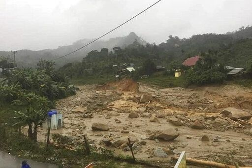 A landslide leaves a trail of rocks and mud as it swamps a village in Phuoc Loc district, Quang Nam province, Vietnam Thursday, Oct. 29, 2020. Three separated landslides triggered by Typhoon Molave killed more than a dozen villagers in the province as rescuers scramble to recover more victims. (Lai Minh Dong/VNA via AP)