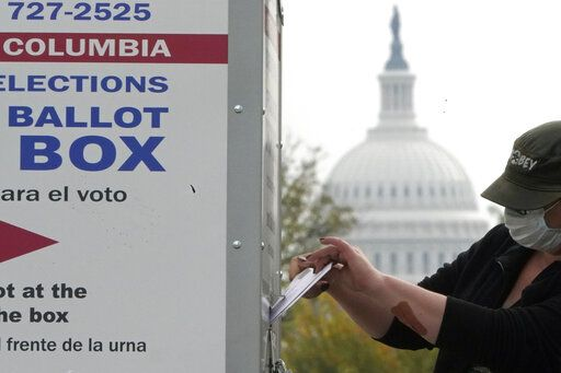 With the U.S. Capitol dome visible, a voter drops a ballot into an early voting drop box, Wednesday, Oct. 28, 2020, at Union Market in Washington.
