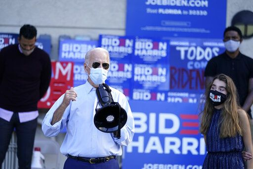 Democratic presidential candidate former Vice President Joe Biden, accompanied by his granddaughter Natalie Biden, speaks to people outside a campaign victory center, Thursday, Oct. 29, 2020, in Fort Lauderdale, Fla.