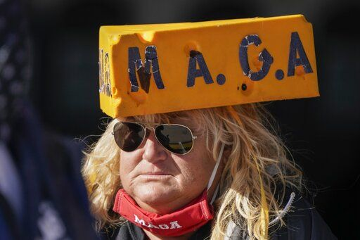 A supporter waits for President Donald Trump to speak at a campaign rally Friday, Oct. 30, 2020, at the Austin Straubel Airport in Green Bay, Wis.