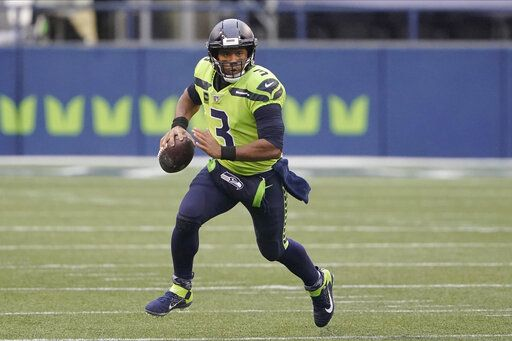 FILE - In this Oct. 11, 2020, file photo, Seattle Seahawks quarterback Russell Wilson looks for a receiver during the first half of the team's NFL football game against the Minnesota Vikings in Seattle. Wilson and his Grammy-winning wife, pop singer Ciara, are putting their money and celebrity behind rebranding a charter school, which advocates hope will boost the troubled Washington state charter school sector that has suffered from enrollment problems after years of legal challenges.