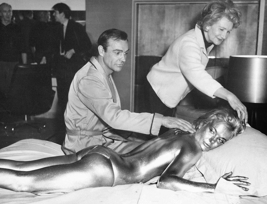"FILE -- In this file photo dated April 20, 1964, James Bond, alias, Sean Connery, finds himself in a sticky situation with actress Shirley Eaton at Pinewood Studios, near London. Miss Eaton was given a liberal coating of gold paint for a scene in the latest Bond thriller ""Goldfinger,"" with unidentified woman at top. Scottish actor Sean Connery, considered by many to have been the best James Bond, has died aged 90, according to an announcement from his family."