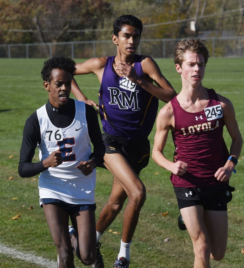 Rolling Meadows' Stephen Barretto runs between Evanston's Essay Tolosa, left, and Loyola Academy's Spencer Werner during the Class 3A Hoffman Estates cross country sectional Saturday.