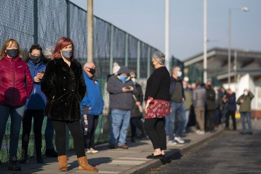 Members of the public queue at Liverpool Tennis Centre on the first day of the pilot scheme of mass testing in Liverpool, Friday Nov. 6, 2020. Liverpool is the pilot project for possible weekly testing of the entire population covering up to 10 million people across England a day. ( AP Photo/Jon Super)