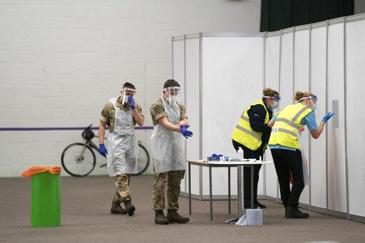 Members of the armed forces help to test the public at Liverpool Tennis Centre on the first day of the pilot scheme of mass testing in Liverpool, Friday Nov. 6, 2020. Liverpool is the pilot project for possible weekly testing of the entire population covering up to 10 million people across England a day. ( AP Photo/Jon Super)